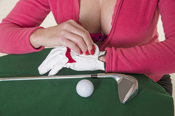 Female golfer putting on her golf glove