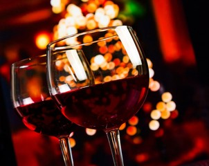 two red wine glass on christmas lights decoration background