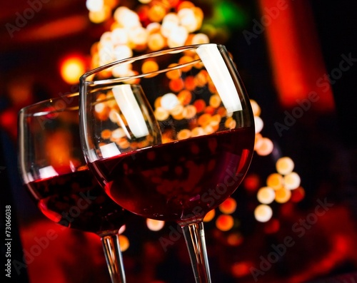 Bar two red wine glass on christmas lights decoration background