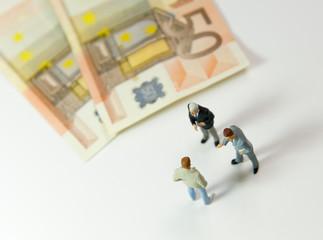 3 hommes discutant à côté de 2 billets de 50€