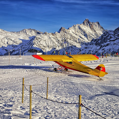 Yellow red airplane at the mountain ski resort airfield in swiss