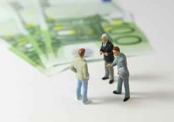 3 hommes discutant à côté de 300 euros
