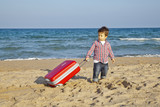 Niño pequeño arrastrando maleta por la arena de la playa