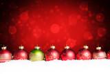 Weihnachtskugeln im Schnee vor weihnachtlichem Hintergrund