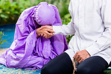 Asian Muslim couple, man and woman, praying at home