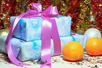 Новогодние подарки и мандарины на фоне елочной гирлянды