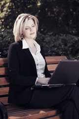 Young businesswoman with laptop in a city park