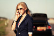 Young fashion woman with broken car calling on the cell phone