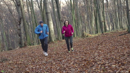 Couple jogging uphill in autumn forest, super slow motion