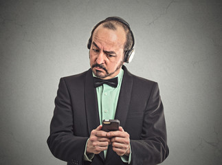 Confused man listening music with headphones on smartphone