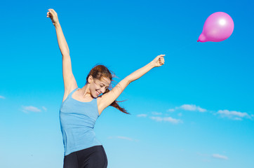 happy smiling woman arms raised with flying air balloon