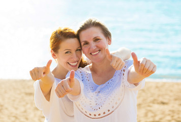 Joyful mother daughter showing thumbs up having fun on beach