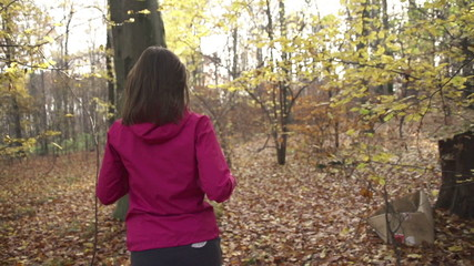 Woman jogging in forest during autumn, super slow motion