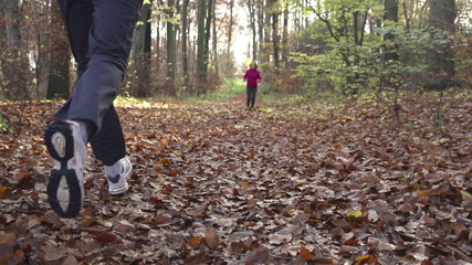 People jogging in autumn forest, super slow motion