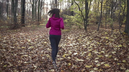 Woman jogging in autumn forest