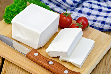 Feta with tomato and knife on wooden board