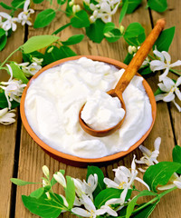 Yogurt in clay bowl with spoon and flowers of honeysuckle