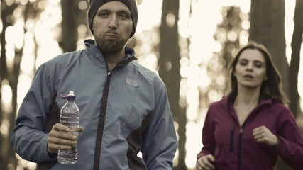 Man drinking water and woman jogging in forest,super slow motion