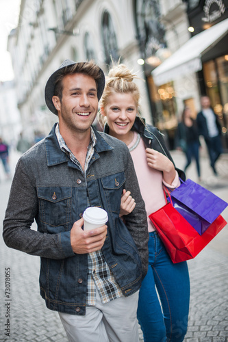 a trendy young couple walks in the city, the young woman has sho - 73078055