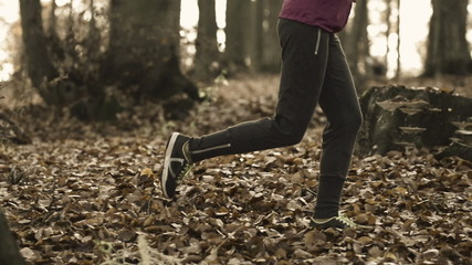 Young woman jogging in forest during autumn, super slow motion