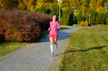 Woman running in autumn park, beautiful girl runner jogging