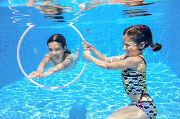 Happy active kids swim in pool and play underwater having fun