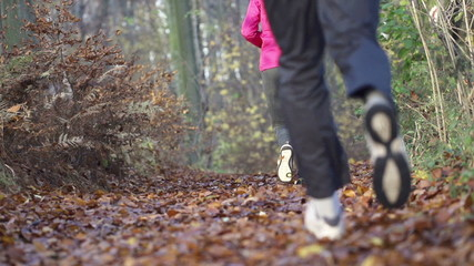 People legs jogging in autumn forest