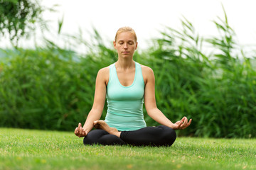 Woman meditating in pose of lotus