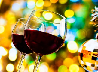 red wine glasses on colorful bokeh and disco ball background