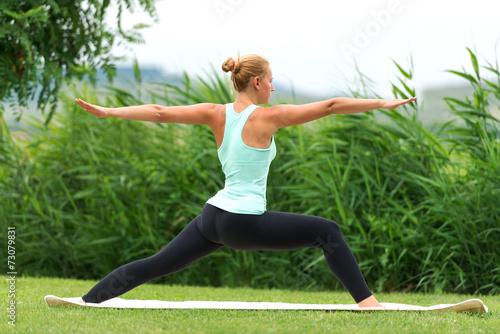 Yoga virabhadrasana II warrior pose by woman