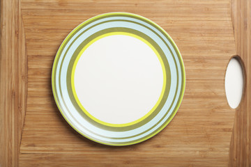 Empty white plate on wooden board