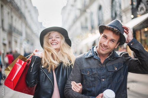 a trendy young couple  wearing hats walking in the city in autum - 73082642