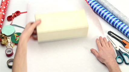 Wrapping christmas gifts on white background