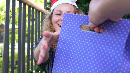 Happy Woman in Santa Hat Receives Christmas Present near X-mas