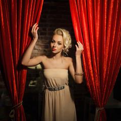 beautiful girl in evening dress posing near a theater curtain