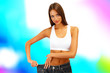Beautiful young woman with big jeans on bright background