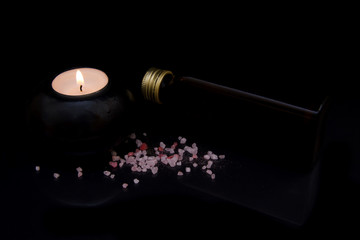 Candle with bath salts and oil on black background
