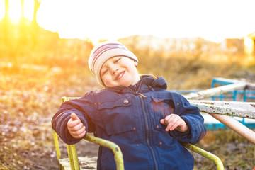 little boy on the old carousel kachaetsya sunny autumn day