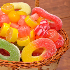 Bright sweets, lollipops, jellies in the wicker basket