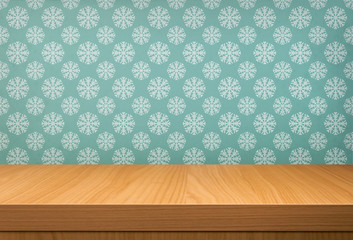 Empty wooden table over vintage wallpaper with a pattern of snow