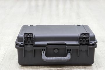 Closed plastic black watertight case on floor