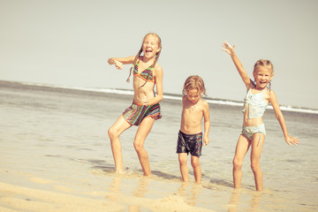 three happy kids playing on beach