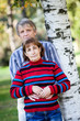 Man and woman of middle age standing in park with back to tree