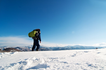 Mountaineer reaches the top of a snowy mountain.