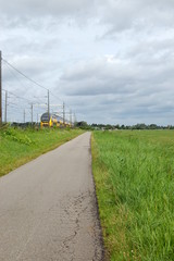 Cycle path along a train track and fields