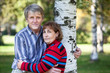 Embracing mature husband and wife standing next to tree in park