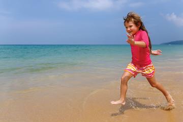 Little girl runs along the beach