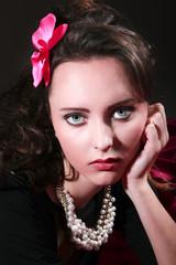 Hübsche junge Frau gut geschminkt mit Halskette blickt verträumt