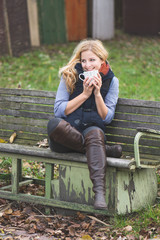 Smiling fashionable blonde drinking coffee or tea outdoors