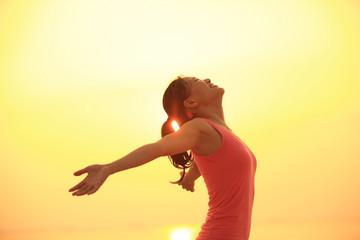 Cheering woman open arms on sunrise seaside
